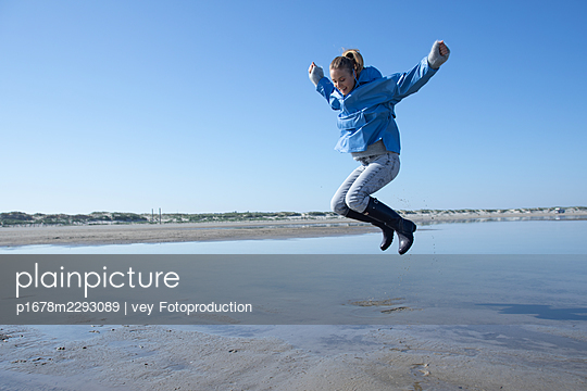 Woman taking a walk by the sea - p1678m2293089 by vey Fotoproduction