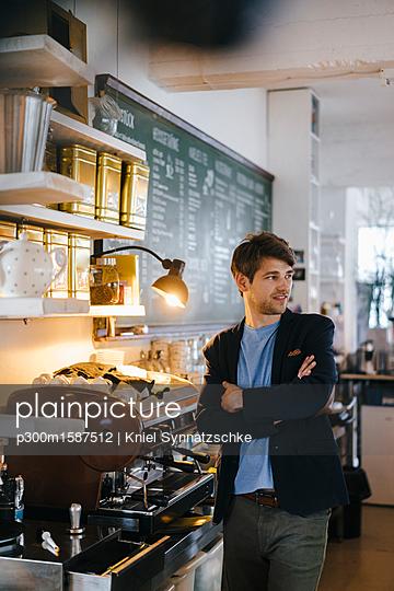 Man in a cafe looking around - p300m1587512 von Kniel Synnatzschke