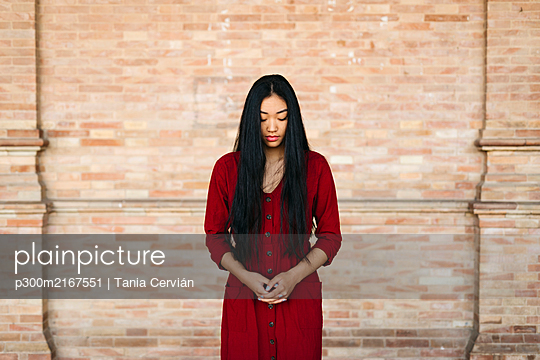 Portait of beautiful young woman wearing a red dress in front of a brick wall - p300m2167551 by Tania Cervián