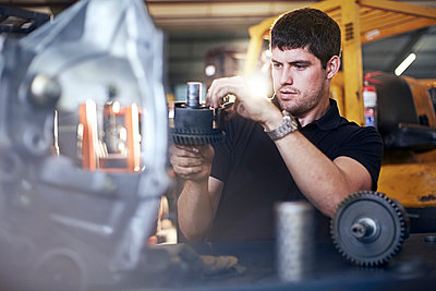 Mechanic examining part in auto repair shop - p1023m1058921f by Trevor Adeline