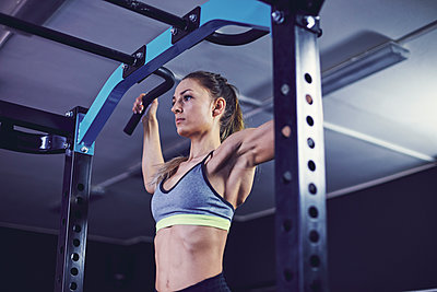 Front profile of young woman doing chin ups at fitness centre - p1166m2095488 by Cavan Images