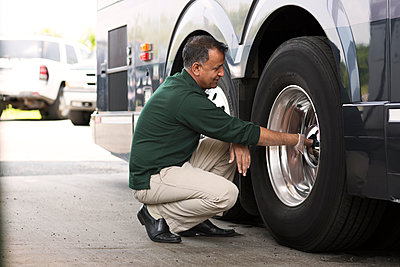 Man examining bus tire at workshop - p1166m995288f by Cavan Images