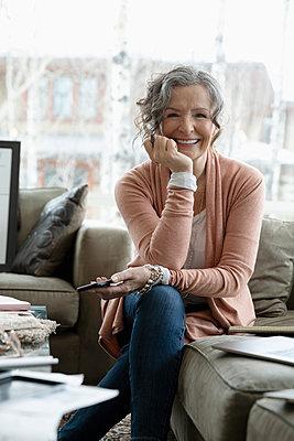 Portrait smiling, confident female senior interior designer on living room sofa - p1192m2088251 by Hero Images