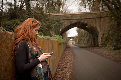 Beautiful woman using mobile phone on a countryside road - p1315m2014258 by Wavebreak