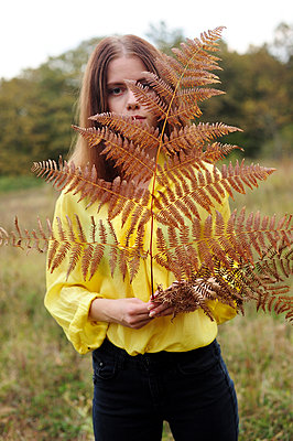 Teenage girl in yellow blouse holding fern in hand - p1412m2128860 by Svetlana Shemeleva