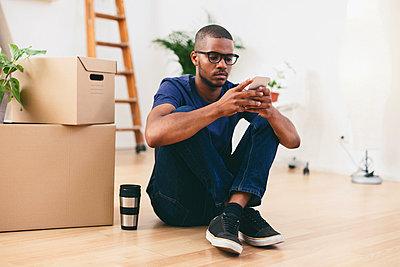 Young man sitting beside cardboard boxes having a break - p300m1052815f by Bonninstudio