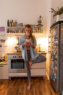Young woman in yoga pose checking cell phone in kitchen at home - p300m2131943 by Gustafsson