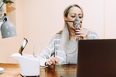 Senior woman with eyes closed using nebulizer during online consultation at home - p300m2240405 by Eloisa Ramos
