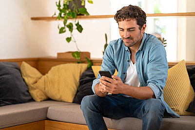 Mid adult man looking at mobile phone on couch at home - p300m2276463 by Steve Brookland
