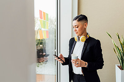 Female entrepreneur holding disposable coffee cup while using smart phone in office - p300m2282341 by Eugenio Marongiu