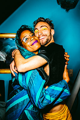 Portrait of happy male and female friends hugging with cheek to cheek in apartment - p426m2279722 by Maskot