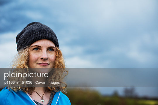 Thoughtful female athlete looking away against cloudy sky - p1166m1151036 by Cavan Images