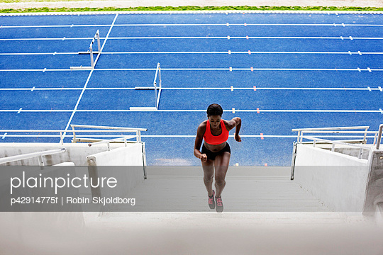 Woman running up stadium stairs - p42914775f by Robin Skjoldborg