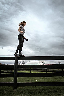Girl in boots finds her balance on Wood Fence  - p1019m1122376 by Stephen Carroll