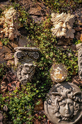 Garden ornaments with faces hanging on a stone wall - p1047m1215469 by Sally Mundy