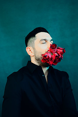 Man with roses in his mouth - p1521m2157603 by Charlotte Zobel