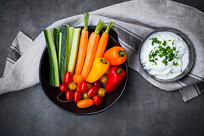 Bowl of chive dip, cherry tomatoes and various vegetable sticks - p300m1562491 by Larissa Veronesi