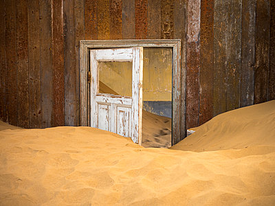 Africa, Namibia, inside a house of ghost town Kolmanskop, wooden door and sand - p300m1579393 by Roy Jankowski