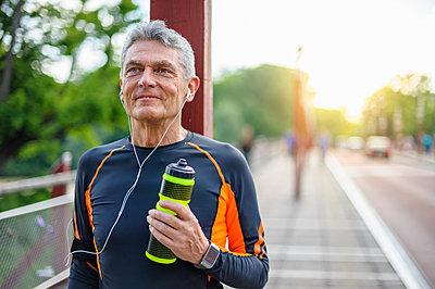 Senior male runner on sidewalk with water bottle - p429m1155449 by Daniel Ingold