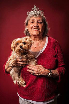 Senior woman holding dog and wearing a tiara - p924m734687 by Raphye Alexius