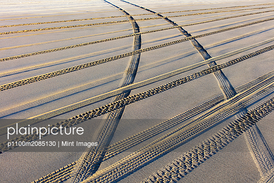 Tire tracks on the soft surface of sand on a beach.  - p1100m2085130 by Mint Images