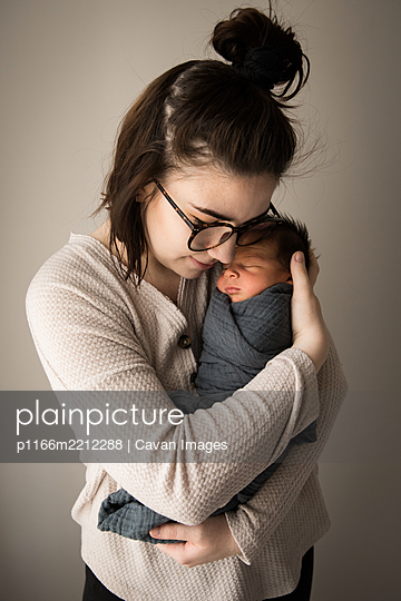 Portrait of Hipster Millennial Mom Snuggling Swaddled Newborn Son - p1166m2212288 by Cavan Images