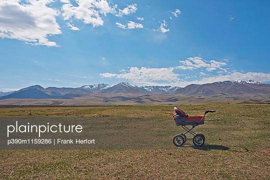 Kinderwagen auf einer Wiese vor den Bergen - p390m1159286 von Frank Herfort