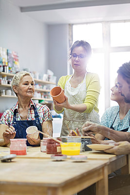 Teacher guiding mature students painting pottery in studio - p1023m1173719 by Agnieszka Olek