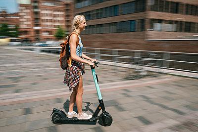 Junge Frau unterwegs mit dem E-Scooter - p299m2108613 von Silke Heyer