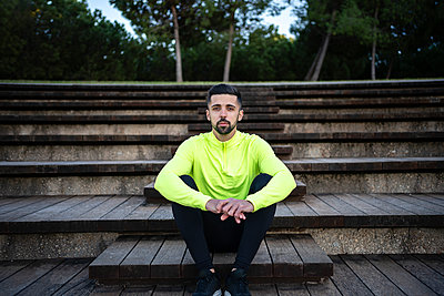 Male sportsperson sitting on staircase at park - p300m2250381 by Albert Martínez