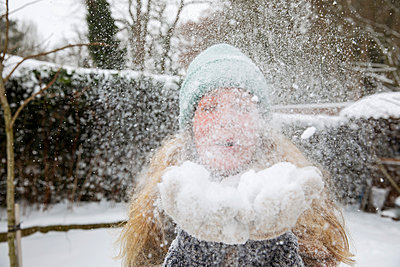 Playful mature woman blowing snow while standing at backyard during winter - p300m2287419 by Frank van Delft