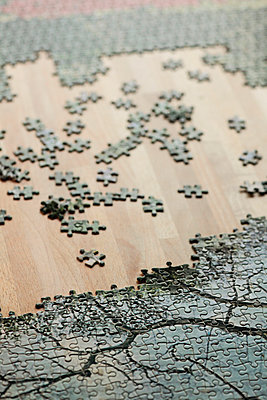 High angle view of jigsaw puzzle and pieces on wooden table - p301m1180717 by Marc Volk