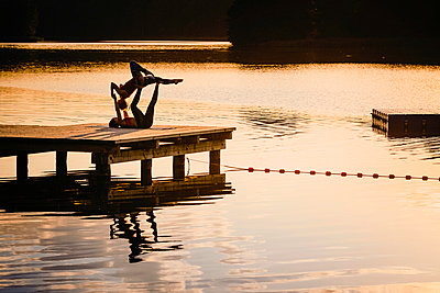 Women practicing acro yoga on lakeside dock at dusk - p301m2075551 by Sven Hagolani