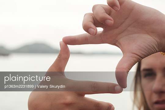 Woman makes a frame with her fingers - p1363m2231899 by Valery Skurydin