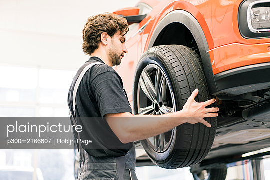 Car mechanic in a workshop changing tire - p300m2166807 by Robijn Page