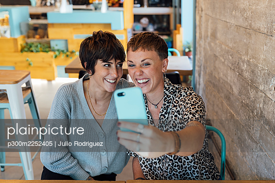young women taking a selfie in the table of a restaurant - p300m2252405 von Julio Rodriguez
