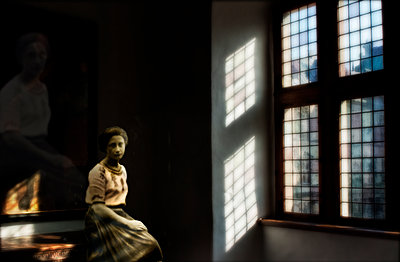 Sad woman sitting in light and shadow - p1693m2294579 by Fran Forman