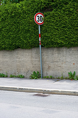 Road sign besides a hedge on pavement - p300m1053158f by visual2020vision