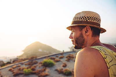 Greece, Milos, Man with straw hat looking at distance - p300m1205870 by Gemma Ferrando