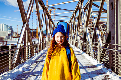 Smiling girl with guitar standing on bridge against sky during winter - p300m2266337 by Irina Heß