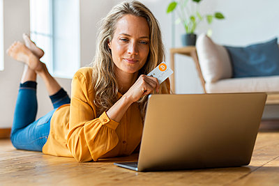Beautiful mid adult woman holding bitcoin credit card while looking at laptop on floor - p300m2277475 by Steve Brookland