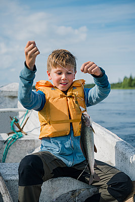 Boy with fish in boat - p312m1533308 by Hans Berggren
