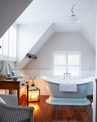 Louvered blinds in attic bathroom with freestanding tub - p349m790248 by Brent Darby