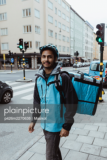 Portrait of smiling delivery man standing on sidewalk in city - p426m2270638 by Maskot