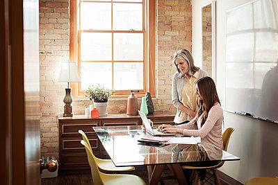 Businesswomen using laptop in board room - p1166m1141472 by Cavan Images