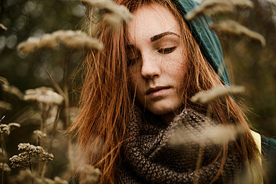 Thoughtful teenage girl with red head standing amidst plants - p1166m2113116 by Cavan Images
