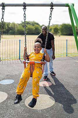 Father with happy daughter swinging on a playground - p300m2154833 by Francesco Buttitta