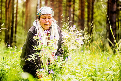 Caucasian woman gathering wildflowers in forest - p555m1412355 by Aleksander Rubtsov