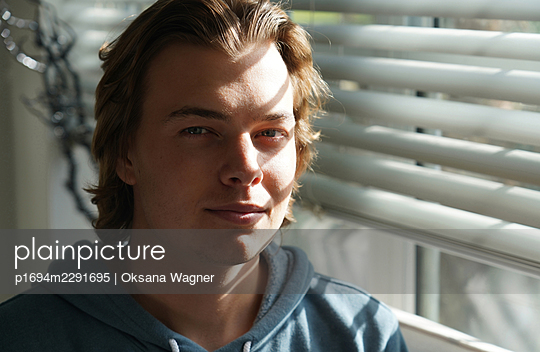 Happy young man with sun shadows on his face sitting next to a sunny window with blinds - p1694m2291695 by Oksana Wagner