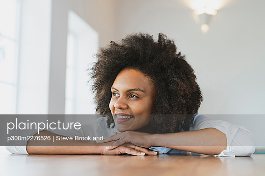Smiling woman leaning on table at home - p300m2276526 by Steve Brookland